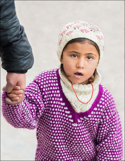 A young girl holds on to her father's hand tightly as they navigate the crowds.